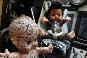 Two dolls with some interesting tattoos.