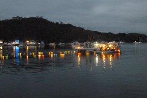 Лодочники опускают фонари на озеро