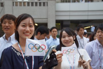 Supporters flash Olympic flags while eagerly awaiting the reveal.