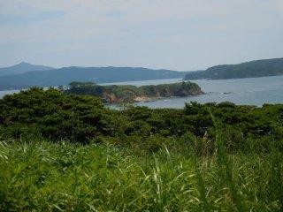 Hai hòn đảo, hòn đảo nhỏ không tên, và đảo Ajishima bên phải. Bán đảo bên trái là Oshikahantou. Trên đỉnh núi phía sau Oshikahantou là Kinkasan.