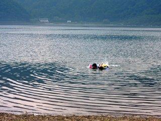 Crianças a mergulhar nas águas rasas