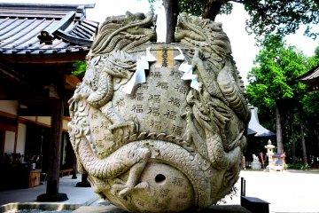 Два дракона вцепились в вырезанный каменный шар