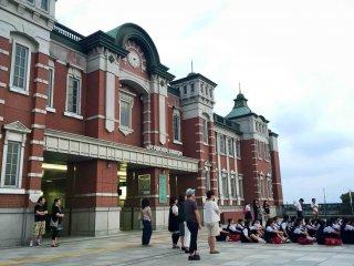 Sekelompok paduan suara sedang berkumpul di halaman luas stasiun