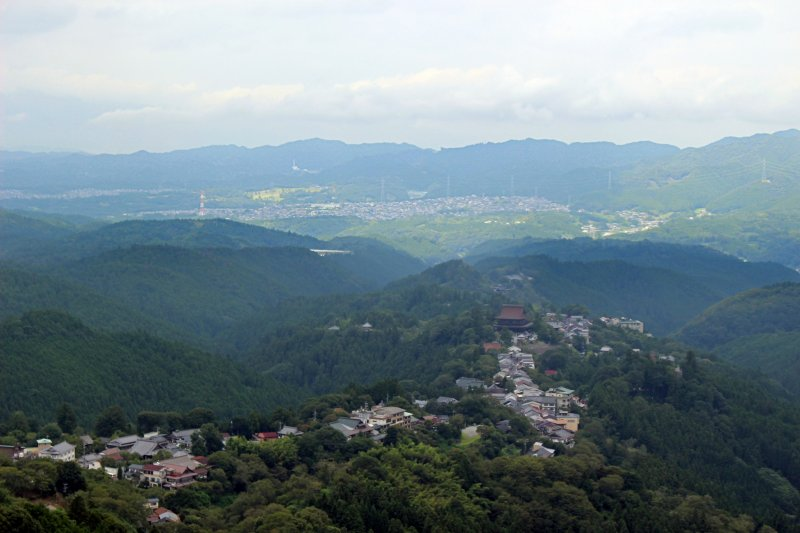 <p>Kinpusenji Temple towers over all of the Town of Yoshinoyama and appears to stop the towns down hill flow against the backdrop of Oyodo Town and the other mountains of Nara</p>