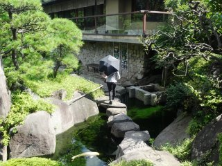 A woman crosses a path of stepping stones in front of the teahouse
