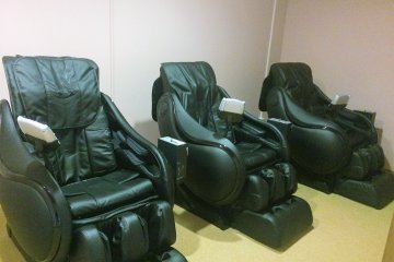 <p>Three massage chairs outside of the onsen</p>