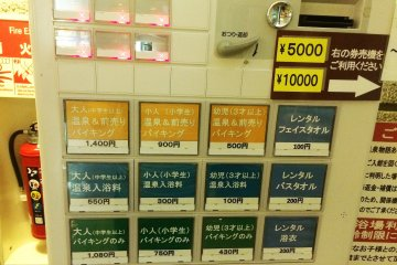 <p>The machine to buy your ticket. The top row of yellow buttons are tickets for both the entrance into the hot spring and lunch buffet. Starting from left to right is the price for adults (¥1,400), elementary age kids (¥900)&nbsp;and young children over the age of 3 (¥500). The middle row of blue buttons is entrance into the hot spring only, and the bottom row of green buttons is for the buffet only. &nbsp;The row of blue buttons on the right side is for rentals. The top one is face towel rental (¥100), the middle is bath towel (¥200), and the bottom is for a Japanese robe (¥200)</p>