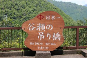 The commemorative plaque noting the length (297.7 meters) and height (54 meters) and that it the longest bridge of its kind in Japan