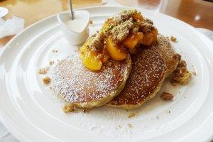 Pancake dengan topping musiman dengan persik dan dtaburi kacang streusel