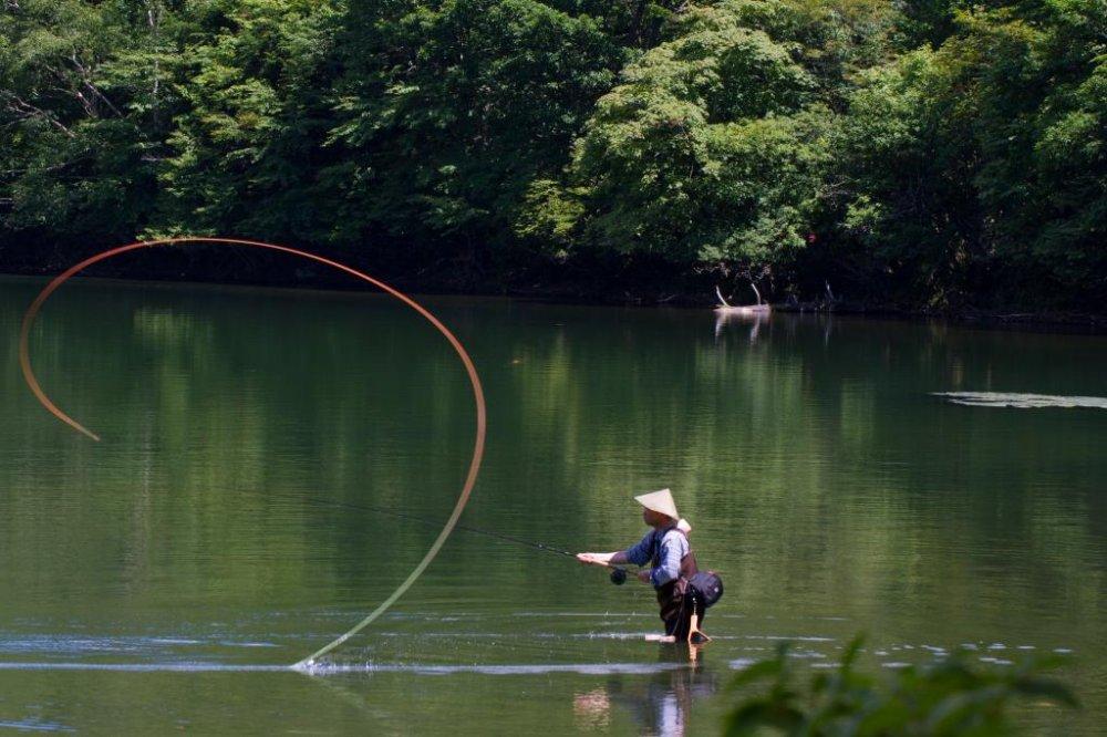 Angler throwing his fishing rod at Yuno-ko (Lake Yuno) in Oku-Nikko