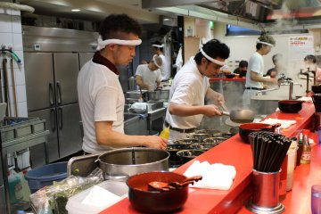 <p>Chefs hard at work preparing a dozen ramen servings at once.</p>