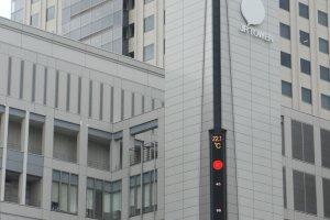 Logo JR Tower dan indikator udara di bagian luar gedung.