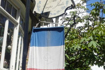 <p>A French tricolor hangs beneath the sign for the restaurant</p>