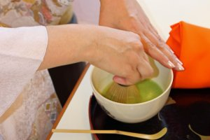 The bamboo tea whisk and back and forth movement of her hand makes the tea frothy