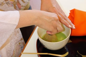 <p>The bamboo tea whisk and back and forth movement of her hand makes the tea frothy</p>