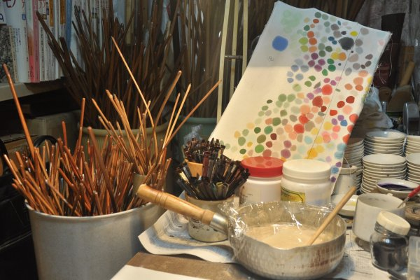 Wooden sticks, used to frame up a piece of cloth, glue and paintbrushes are readily available on the table.