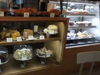 В левой витрине - кексы, маффины и другая выпечка из теста, а в правой - торты с кремом, чизкейки, американский тыквенный пирог