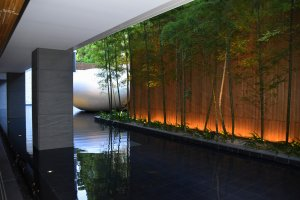 Open-air corridor of the hotel. Bamboo and a moon-shaped sculpture are set in an artificial pond.