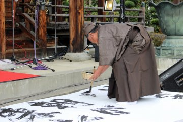 <p>The head of the Imai-cho Neighborhood Association (the organizer of the event) writes out a prayer and message in the welcoming calligraphy performance while a jazz band from the medical university plays a walking number</p>