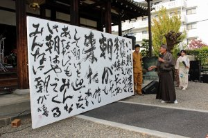 The finished calligraphy is explained by the head of the neighborhood association