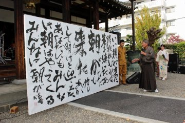 <p>The finished calligraphy is explained by the head of the neighborhood association</p>