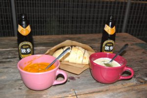 Bowls of chowder and chicken curry with sour dough bread and beer