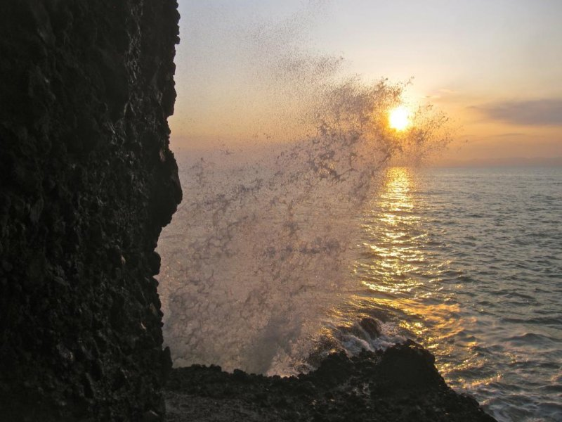 A breaking waves makes a grab for the setting sun