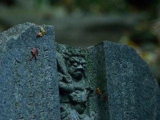 Một bức tượng được bao phủ trong lá mùa thu rơi