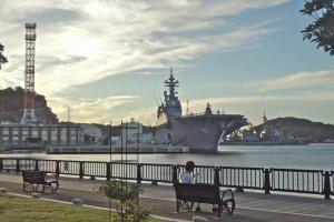 公園ベンチのすぐ目の前に軍艦が碇泊している