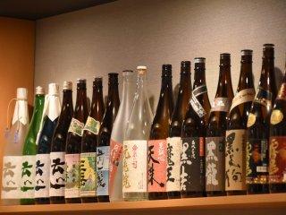 Sake and shochu bottles line the wall shelf