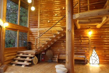 <p>The Log House&#39;s common space. A wood burning fireplace/stove, a swing, enormous windows and stools and pillows for sitting on the floor are available</p>
