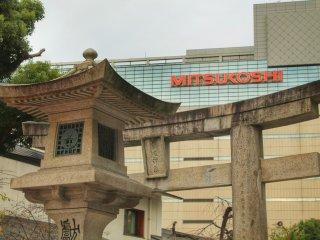 Каменный фонарь и ворота в храм Кэго с Мицукоси на заднем плане