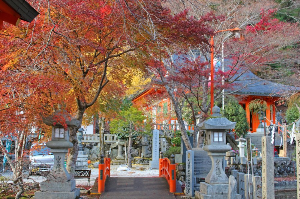 The stone lanterns and fiery leaves form a beautiful gateway over one of the entrance bridges