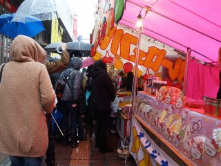 Huddled in raincoats and under umbrellas, locals wait in line for delicious street food.
