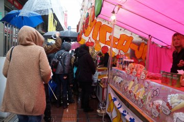 <p>Huddled in raincoats and under umbrellas, locals wait in line for delicious street food.</p>
