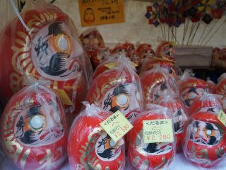 Daruma of various sizes wrapped in plastic to protect them from the rain.