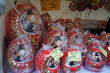 <p>Daruma of various sizes wrapped in plastic to protect them from the rain.</p>