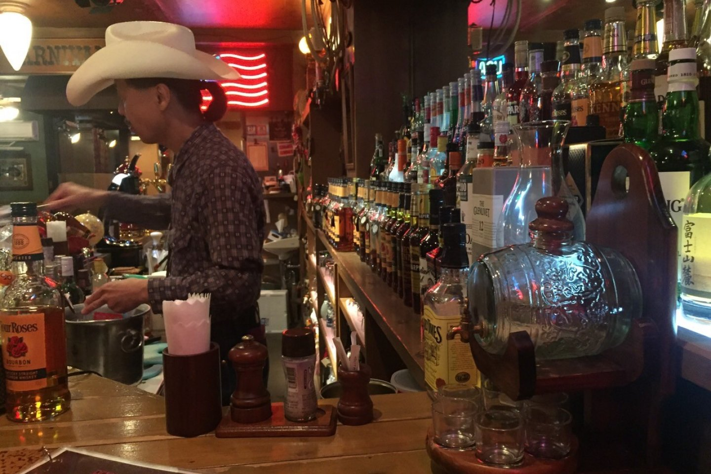 A bartender in a cowboy hat mans the bar area at Steak and Bar Red River in Chiba.