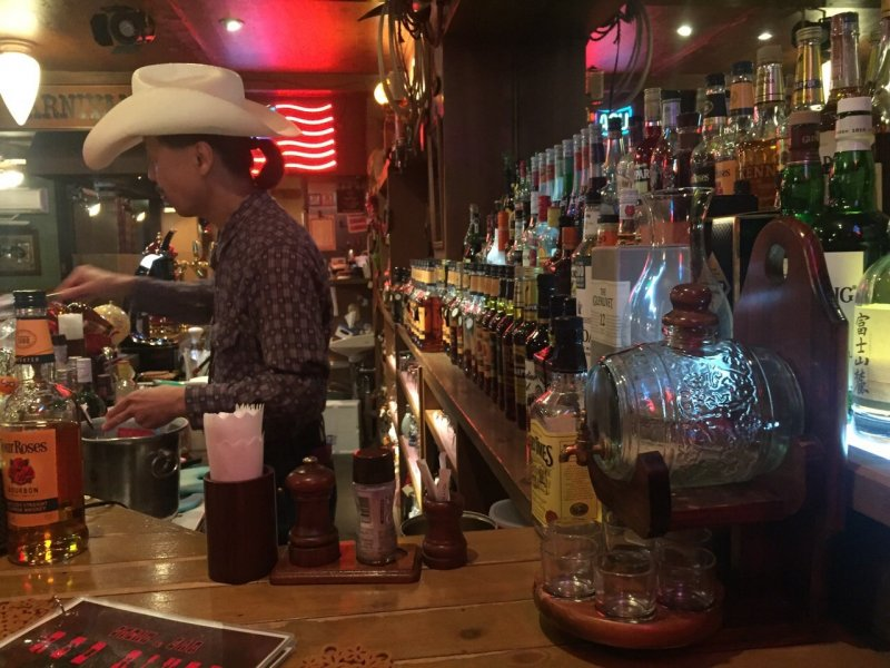 <p>A bartender in a cowboy hat mans the bar area at Steak and Bar Red River in Chiba.</p>