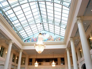 Brilliant lights are coming through the glass ceiling into the hotel lobby