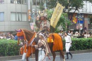 Samurai on horseback parading through the city streets