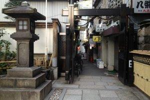 Salah satu pintu masuk area kuil yang mengarah ke gang berisi toko-toko