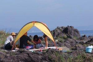 小さなテントを張って海辺でくつろぐ家族連れ