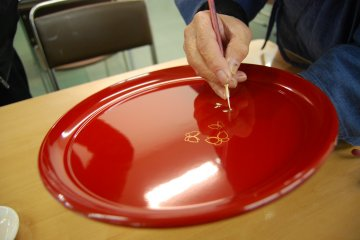 Makie, the painting of lacquerware plates, can be experienced at the Uruwashi-Kan in Kuroe Town.