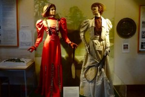Two female mannequins wearing long skirts and holding small rackets