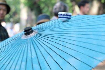Sake cup in motion being balanced on Umbrella