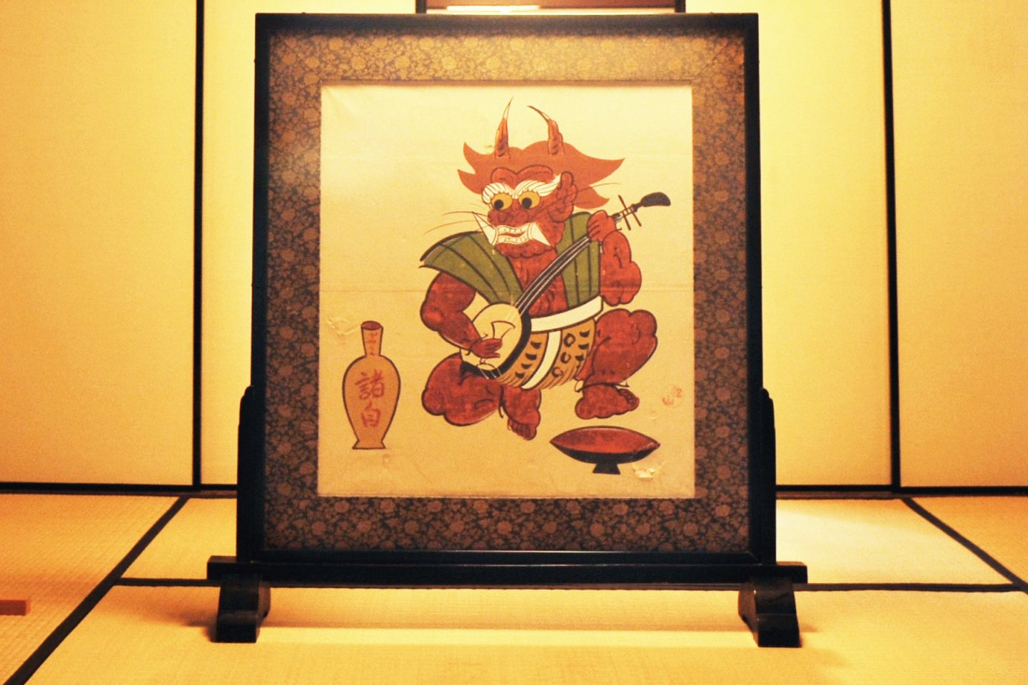 An otsu-e of a mythical goblin playing the shamisen and drinking sake