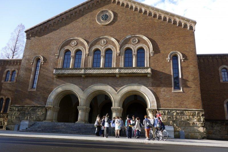 A student social club gathers outside Kanematsu Auditorium