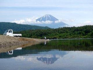 Мужчина забрасывает свою удочку в озеро Сайко в спокойный солнечный день