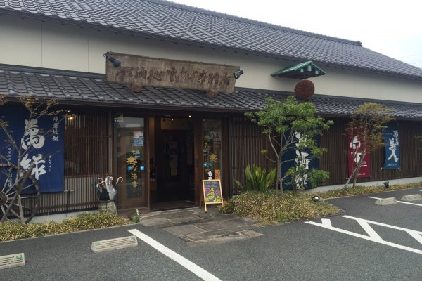 The white wall and tiled roof with the wooden sign for Jizake-dokoro Tachibana store